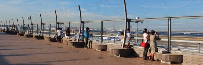 空港のテラスから飛行機を眺める人たち